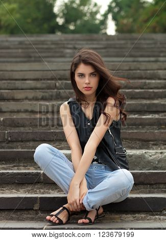 Young beautiful fashionable brunette woman in black leather jacket posing sitting on park stairway