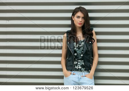 Young calm fashionable brunette woman in black leather jacket posing outdoors against urban style background of metal strips