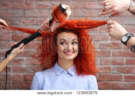 Red haired beautiful girl with many hands and accessories