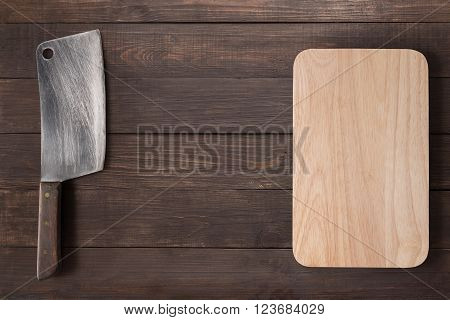 Cleaver and cutting board on the wooden background.