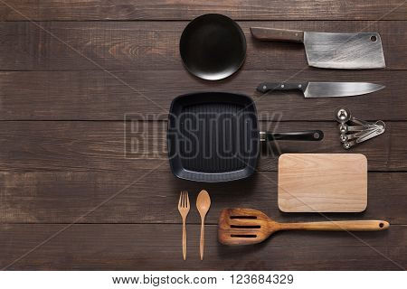 Various kitchenware utensils on the wooden background for cooking.