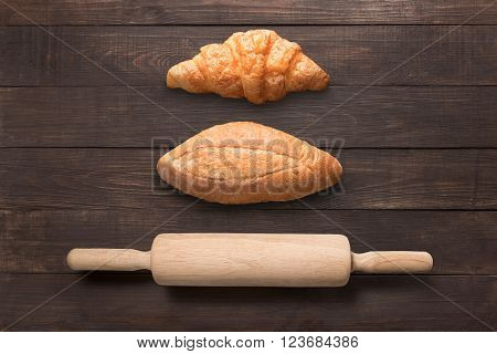 Bread and rolling pin on wooden background from top view.