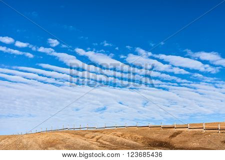 Fence in the steppe Shamanka on cape Burhan. Blue sky over the island Olkhon in the Siberian Lake Baikal in winter. Russia. Ice on Lake Baikal. Horizontal landscape