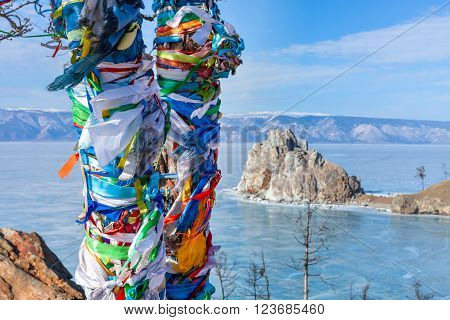Lonely tree on a background of the holy Shamanka on cape Burhan. Russia. Ice on Lake Baikal. Horizontal landscape. Olkhon Island in the Siberian Lake Baikal in winter.