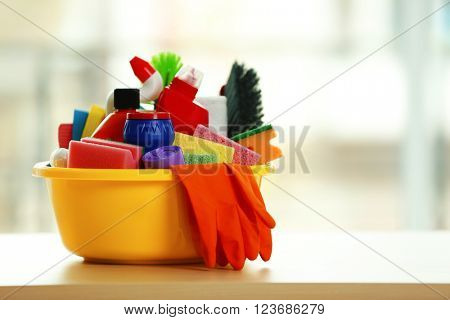 Cleaning set with products and tools in yellow tub