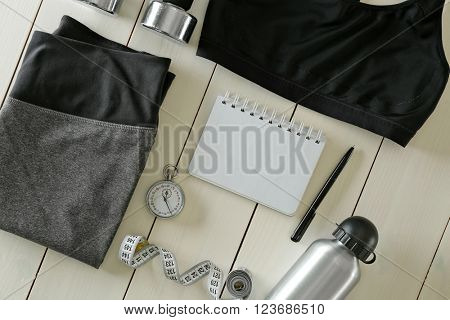 Athlete's set with female clothing, equipment, bottle of water and notebook on white wooden background