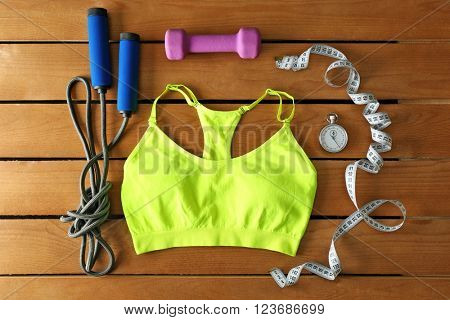 Athlete's set with female clothing and  equipment on wooden background