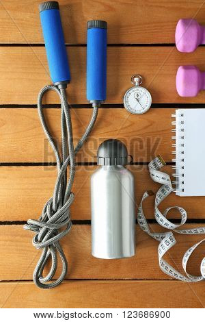 Athlete's set with equipment, bottle of water and notebook on wooden background