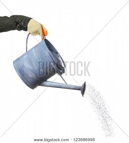 Hand pouring from metal watering can, isolated on white