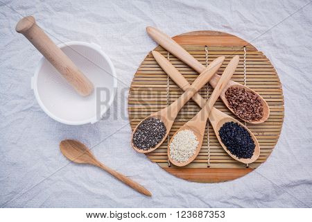 Super healthy of seeds selection flax seed,chia seed ,black sesame and white sesame in wooden spoon setup on wooden background.