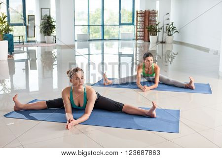 Two young women training twine in the gym