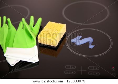 Detergent with protective gloves and sponge on electric hob closeup