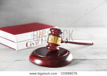 Gavel and books on wooden table on grey background