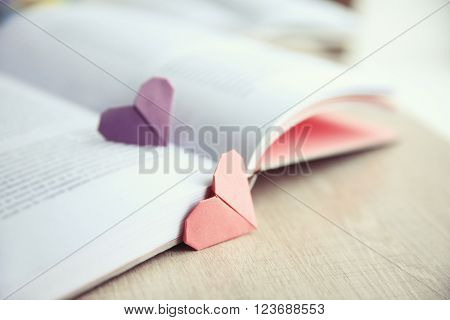 Book and heart shaped bookmarks on a  wooden table