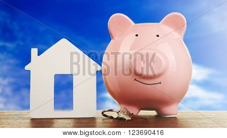 Pig money box and paper decor on a table, blue sky background