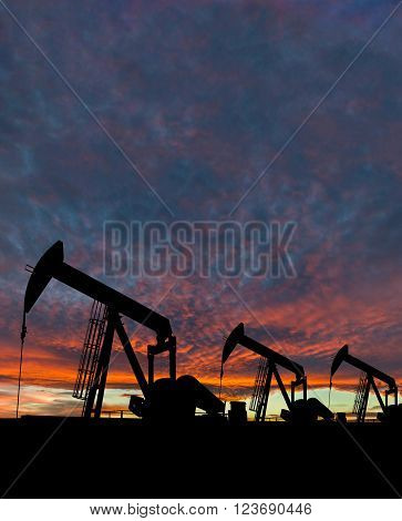 Silhouette Of Pumpjack Against A Dramatic Sky