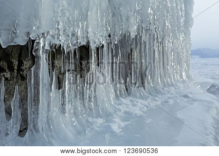 Huge icicles on rocks. Beautiful winter landscape in the Lake Baikal.