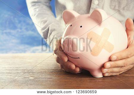 Man holding Piggy Bank with adhesive bandage, on sky background