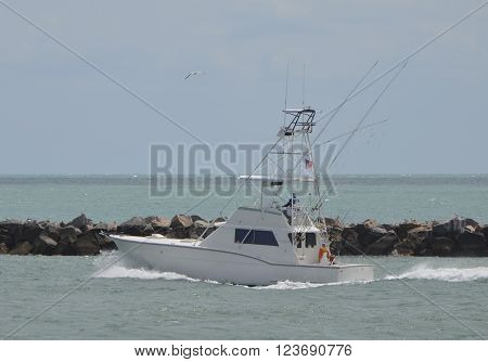 Charter sport fishing boat heading east towards open ocean from it's home port in Miami Beach,Florida