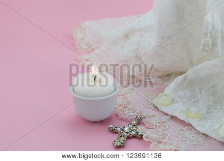 Close up of vintage baptism dress on pink with lit candle.
