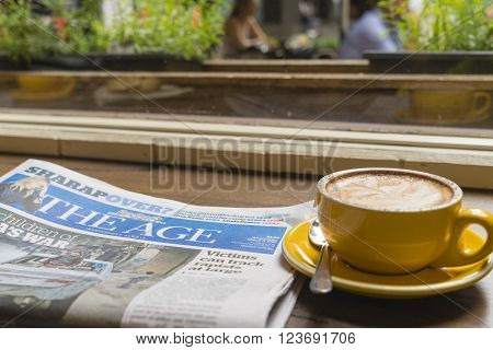 Melbourne, Australia - Mar 9, 2016: Reading The Age newspaper and enjoying coffee in a cafe. The Age is a daily newspaper published in Melbourne, Australia.
