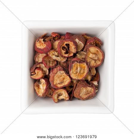 Dried hawthorn fruits in a square bowl isolated on white background