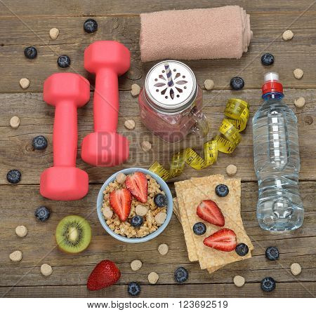 Items for sports on a wooden background fitness and diet concept