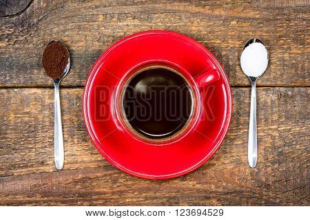 Red coffee cup with coffee and sugar filled spoons on wooden table