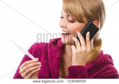 Happy delighted woman wearing purple bathrobe, looking at pregnancy test and talking on mobile phone, informing someone about positive result test, expecting for baby