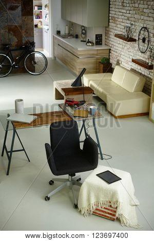Stylish retro home interior with desk, sofa and kitchen.