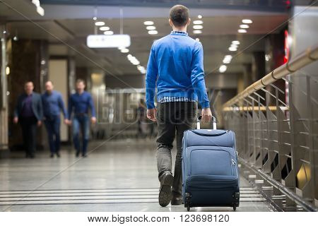 Traveler Pulling Suitcase At Airport