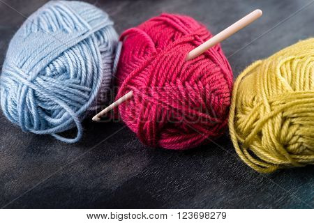 Colorful yarn skeins on the dark wooden background.