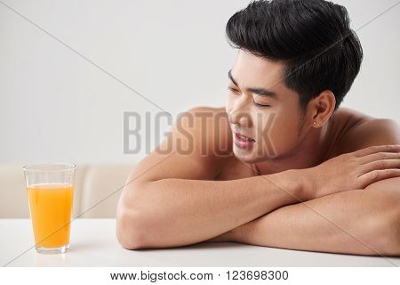 Vietnamese young man looking at glass of orange juice