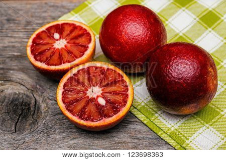 sliced red sicilian oranges on wooden background