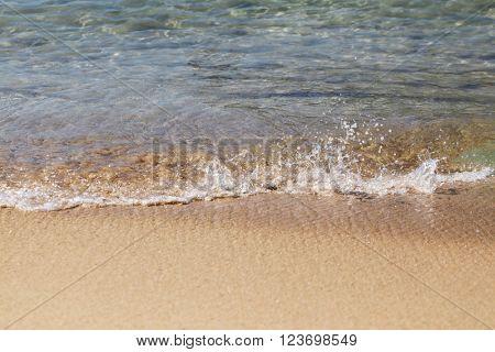 Closeup sea waves coming on beach at sunset light