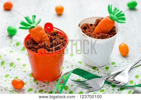 Cute Easter treat for kids decorative sugar carrot chocolate biscuit crumbs cream in the little bucket on white background. Creative holiday sweets selective focus