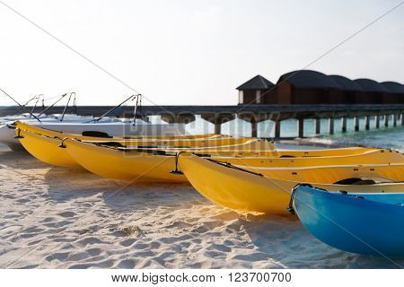 kayaking, leisure, water sport and summer vacations concept - canoes or kayaks mooring on sandy beach