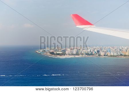 travel, summer vacation, transportation, air transport and vehicle concept - close up of airplane wing flying above Male city on Maldive island in ocean