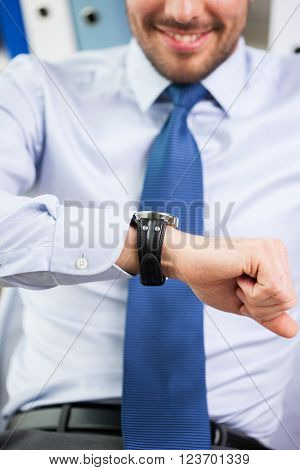 business, people, time management and work concept - close up of smiling businessman looking at his wristwatch in office