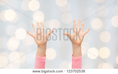 people, childhood, gesture and body parts concept - close up of little child hands raised up over holidays lights background