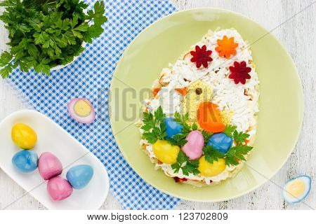Festive Easter Egg salad with a little funny chicken and colored eggs beautiful dish for Easter menu and kids birthday party top view. Food art idea recipe