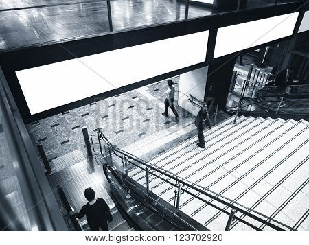 Blank Banner Billboard Media Display with Escalator Stairs and people walk in subway station