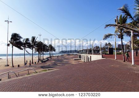 DURBAN SOUTH AFRICA - MARCH 23 2016: Many unknown people walk along paved promenade on Golden Mile beachfront in Durban South Africa