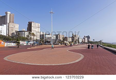 DURBAN SOUTH AFRICA - MARCH 23 2016: Early morning view of many unknown people walking along paved promenade against city skyline in Durban South Africa