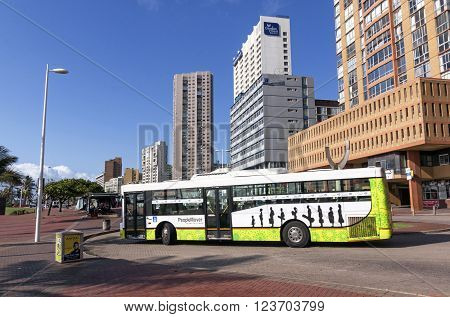 DURBAN SOUTH AFRICA - MARCH 23 2016: Municipal bus navigating through roundabout against city skyline on Golden Mile beachfront in Durban South Africa