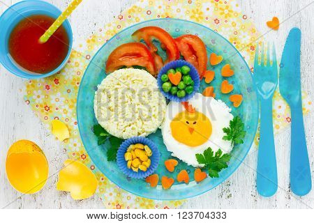 Easter breakfast for the child. Creative idea for baby food - vegetables and fried egg in the shape of chick. Colorful healthy food concept top view