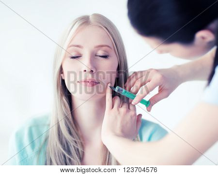 beauty, healthcare and medical concept - beautician with patient doing anti-aging injection in hospital