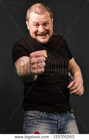 Agressive bully threatens with a fist portrait low key