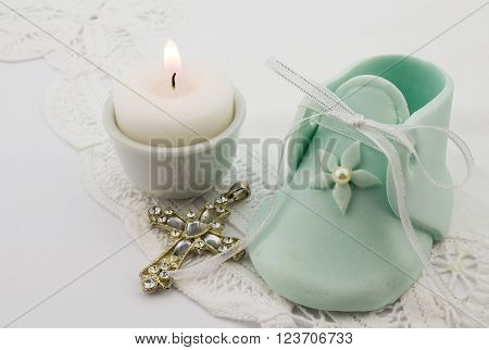Photo of turquoise fondant baby boot with pearlcrystal cross and lit candle isolated on white lace background