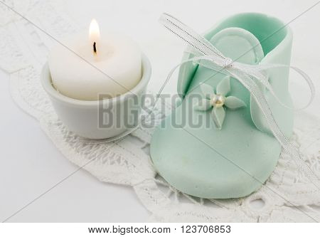 Photo of turquoise baby fondant icing shoe with candle on white lace background